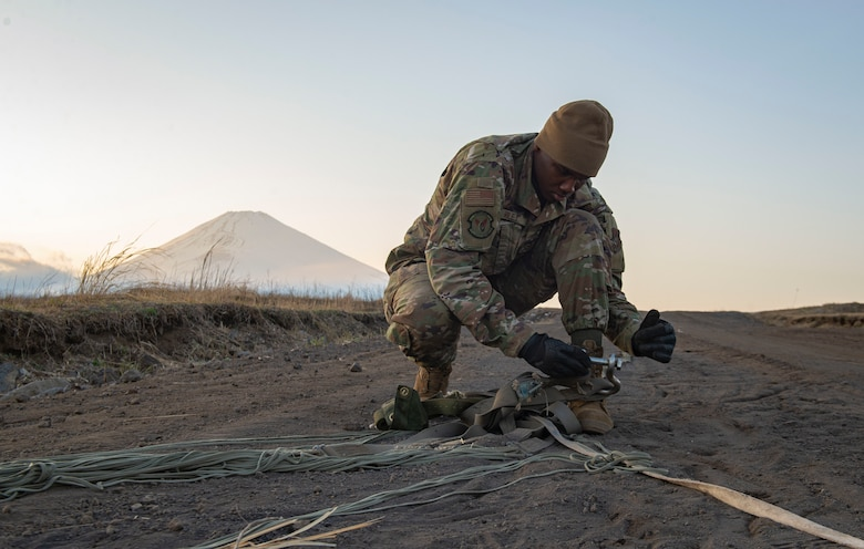 Airman 1st Class Jalen Riley, 374th Logistics Readiness Squadron combat mobility flight technician, removes debris from a canopy and suspension lines before stowing the parachute inside a recovery bag
