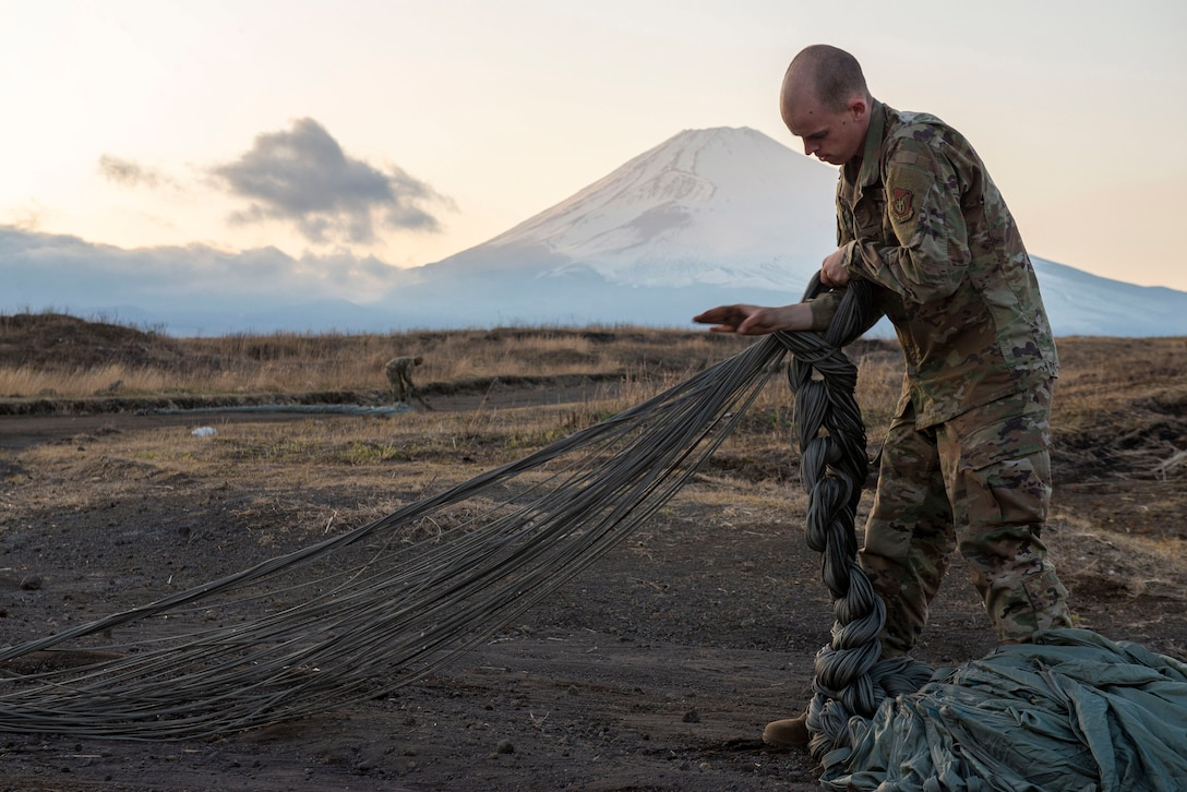 Staff Sgt. Nicholas Adkins, 374th Logistics Readiness Squadron combat mobility flight supervisor, folds parachute suspension lines before stowing the parachute inside a recovery bag