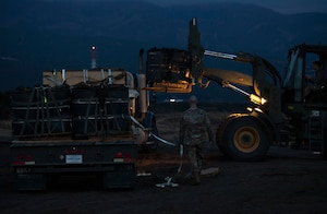 Airman 1st Class Timothy Skelton, 374th Logistics Readiness Squadron vehicle operator, watches as a bundle is loaded onto a trailer
