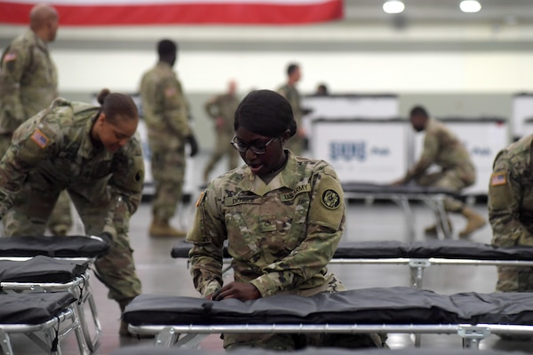 Army Pfc. NDeye Diongue, assigned to the Maryland Army National Guard's 1297th Support Battalion, assembles a cot and bedding as she and other Soldiers set up a federal medical station in the Baltimore Convention CenterMarch 28, 2020. The station was set up to alleviate possible overcrowding at area hospitals as a result of the COVID-19 outbreak.