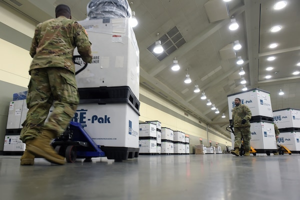 Soldiers with the Maryland Army National Guard move boxes containing bedding and medical supplies into position as they and other Soldiers set up a federal medical station in the Baltimore Convention Center March 28, 2020. They are part of a force of about 15,000 National Guard members on duty nationwide delivering supplies, running mobile testing centers and working with state and local authorities in COVID-19 response efforts.