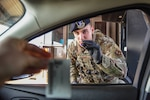 Senior Airman Jacob Stevens, 100th Security Forces Squadron defender, checks a member's identification credentials at the gate while adhering to social distancing requirements on RAF Mildenhall, England, March 25, 2020. Personnel on base have taken extra precautions to prevent the spread COVID-19. (U.S. Air Force photo by Staff Sgt. Luke Milano)