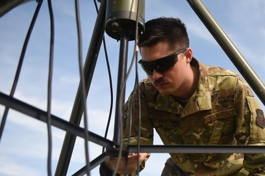 Staff Sgt.Jordan Field, 22nd Operation Support Squadron weather forecaster, checks the level of the tactical meteorological observing system March 26, 2020, at McConnell Air Force Base, Kansas. Field used a bullseye level to ensure the TMQ-53 is level in order to get accurate readings on the wind direction. The TMQ-53 is a portable, automated weather system that makes observations on all types of weather in five second intervals. This information is then sent to a laptop where a forecast can be developed. (U.S. Air Force photo by Senior Airman Alexi Bosarge)
