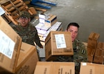 Spc. Alexander Cruz-Martinez and Staff Sgt. Carey Morris, New Hampshire Army National Guard, load boxes of personal protective equipment onto a military cargo truck in Concord, March 30, 2020.  The equipment, to include latex gloves and face masks, was stored in preparation for potential COVID-19 support operations.