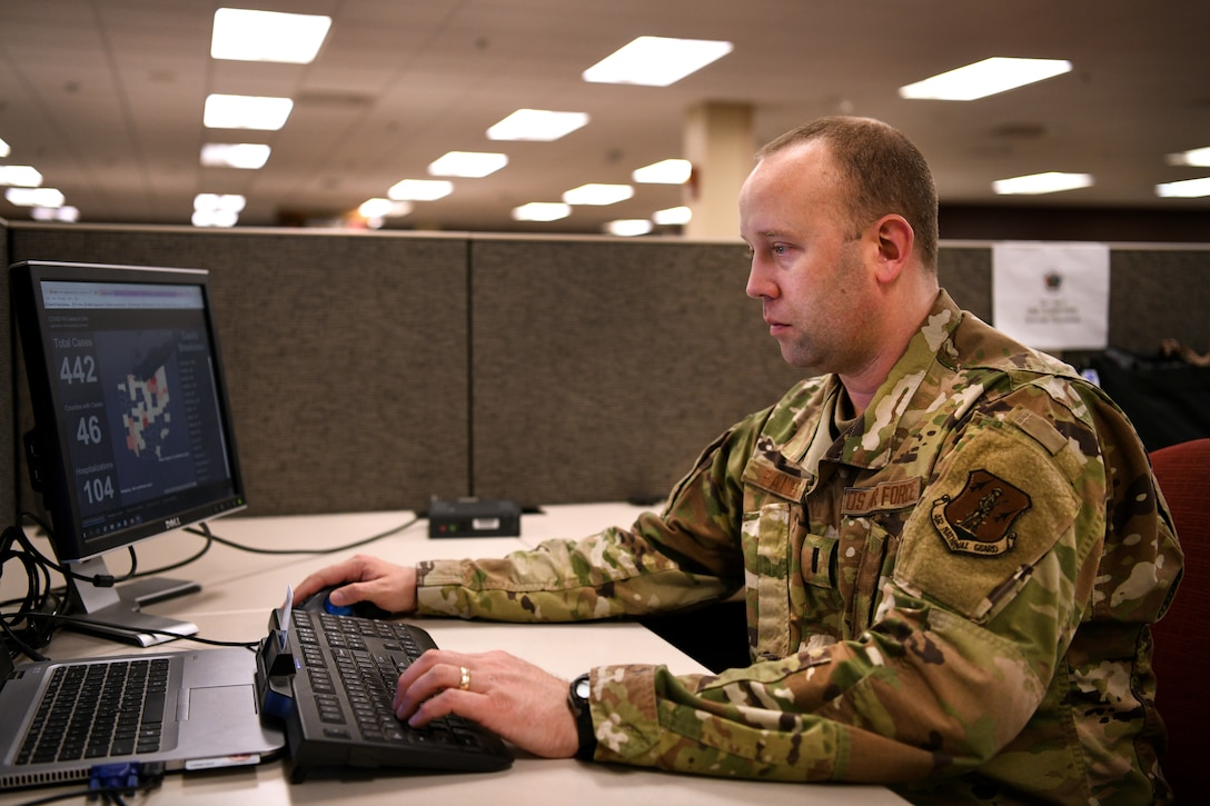 An airman gathers information for a weather report while seated at a computer monitor.
