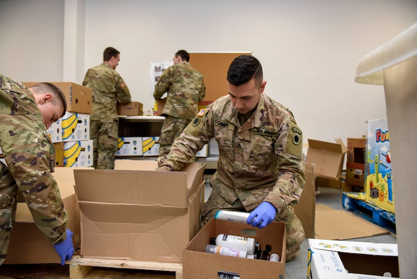 Soldiers wearing blue gloves place donated items into boxes.