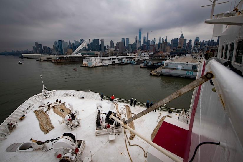 Sailors look at the New York City skyline as their ship arrives.
