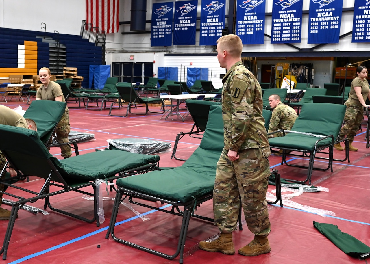 Soldiers set up cots in a gym.