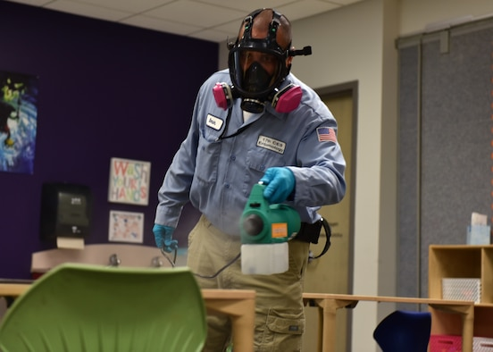 17th Civil Engineer Squadron Pest Controller Omar Martinez, walks around a classroom dispersing a disinfectant mist on all surfaces at Goodfellow Air Force Base, Texas, March 30, 2020. The chemical used is 99 percent effective at bonding to germs on the surface and killing them within the dwell time of 20 minutes. (U.S. Air Force photo by Senior Airman Seraiah Wolf)