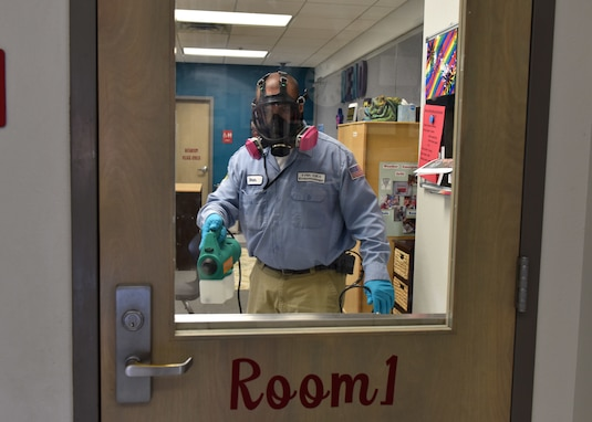 Civil Engineer Squadron Pest Controller Omar Martinez sprays the door to a classroom in the school-age program with disinfectant on Goodfellow Air Force Base, Texas, March 30, 2020. The members of the 17th CES use the fog as a more efficient way to reach every surface in a room. (U.S. Air Force photo by Senior Airman Seraiah Wolf)