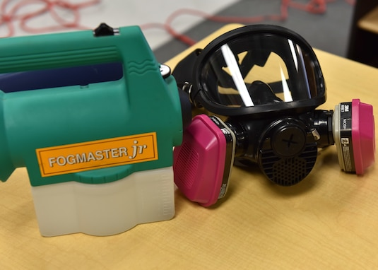 A mask and fogging machine sit on a table before use at the school-age program building on Goodfellow Air Force Base, Texas, March 30, 2020. The chemical used in the machine for disinfecting the rooms is certified as safe to use without the masks but 17th Civil Engineer Squadron members are taking every precaution. (U.S. Air Force photo by Senior Airman Seraiah Wolf)