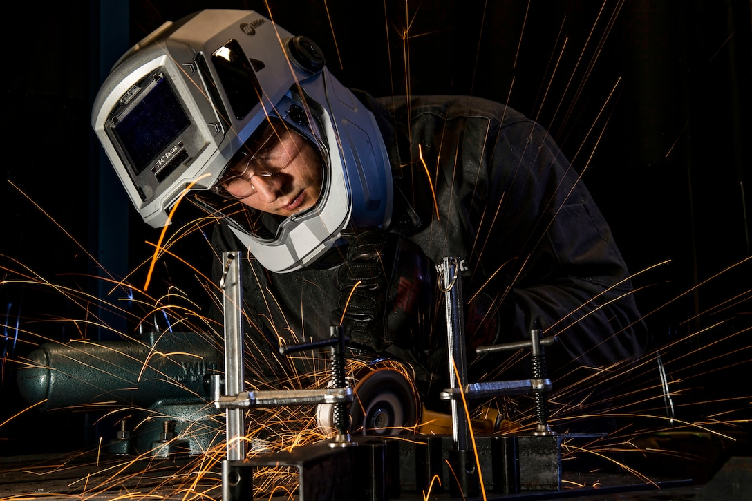 Sparks fly as an airman wearing a helmet welds.