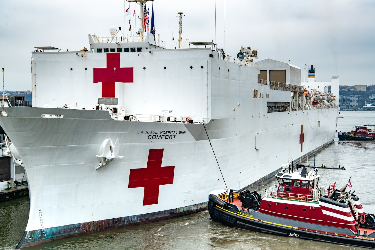 A ship docks with assistance of two boats.