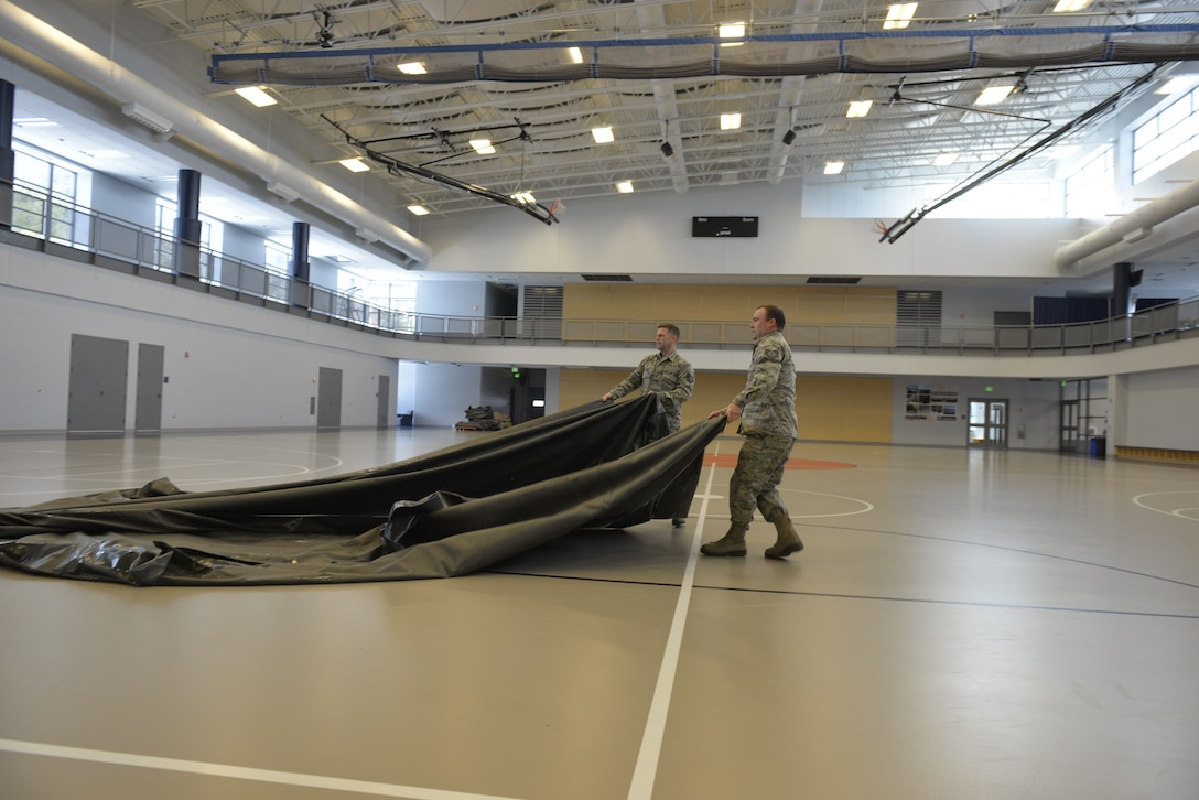"""Tech. Sgt. Mark Quinn and Tech. Sgt. Lance Whitehill, assigned to the 157th Civil Engineer Squadron, New Hampshire Air National Guard, prepare the Hamel Recreational Center floor for medical equipment at the University of New Hampshire, March 25. The facility in Durham will augment area hospitals treating COVID-19 cases, if necessary. It is one of nine """"surge"""" locations the NH Guard, in coordination with local and state healthcare agencies, plans to set up and manage across the state. (U.S. Air National Guard photo by Tech. Sgt. Aaron Vezeau)"""