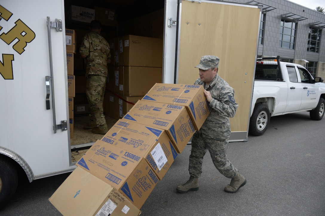 Tech. Sgt. Lance Whitehill, 157th Civil Engineers Squadron, New Hampshire Air National Guard, offloads supplies at the Hamel Recreation Center, University of New Hampshire, March 25, 2020. The facility will augment area hospitals treating COVID-19 cases, if necessary. It is one of nine the NHNG plans to set up and manage across the state. (U.S. Air National Guard photo by Tech. Sgt. Aaron Vezeau)