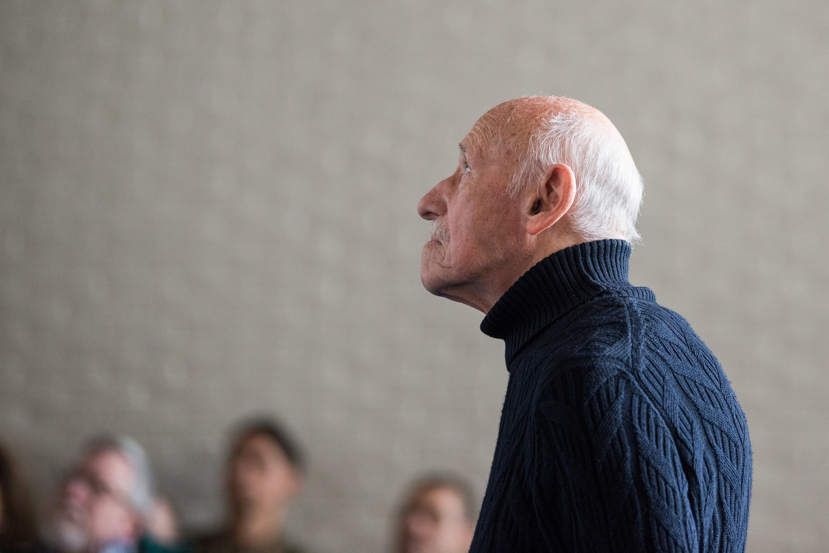 Paul Sobol, survivor of Auschwitz Concentration Camp, watches presentation about horrors of Holocaust during special Holocaust Remembrance Day observance, April 12, 2019, at Supreme Headquarters Allied Powers Europe, Belgium (U.S. Army/Pierre-Etienne Courtejoie)