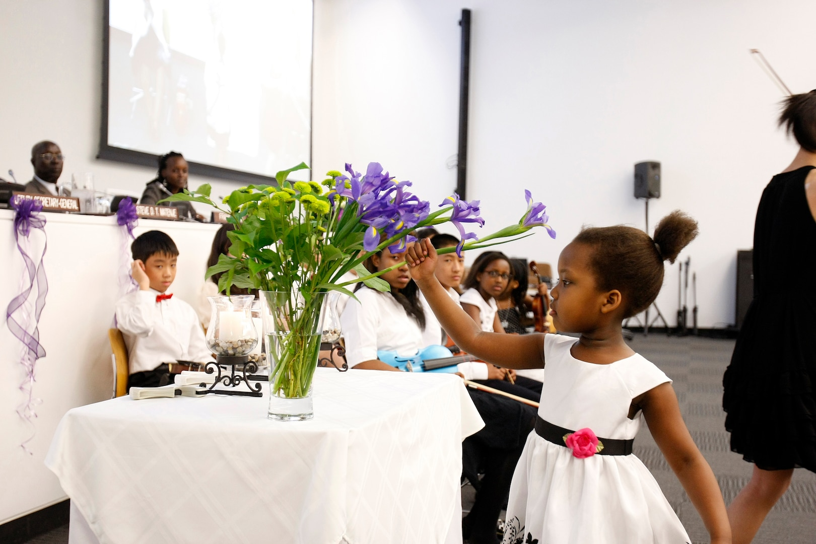 Young girl participates in United Nations Headquarters 16th commemoration of International Day of Reflection on 1994 Genocide in Rwanda, honoring victims of genocide with flowers, United Nations, New York, April 7, 2010 (Courtesy United Nations/Paulo Filgueiras)