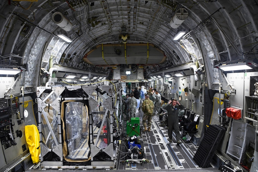 The cargo hold of an aircraft carries several large, metal containers with plastic sheeting for windows.