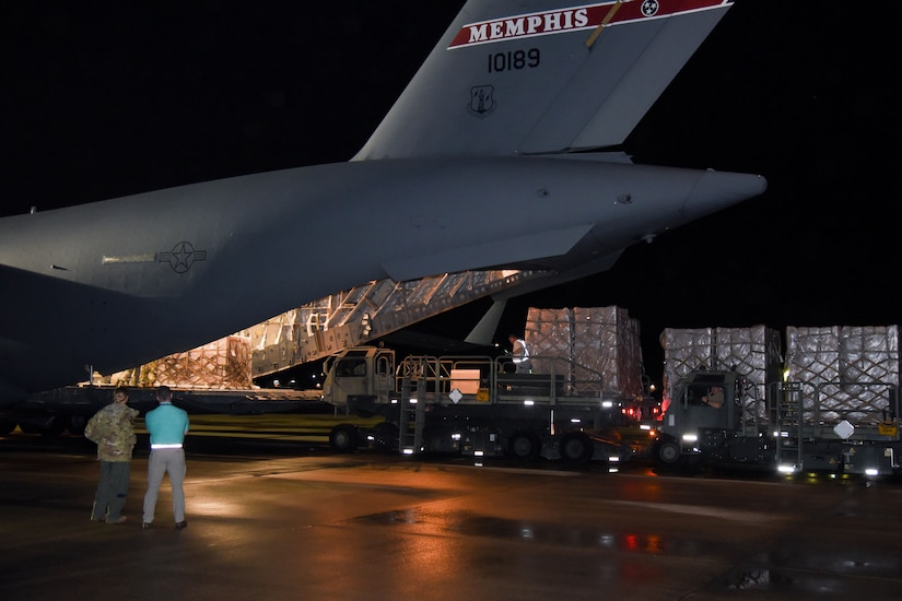 A vehicle unloads pallets from a military aircraft.