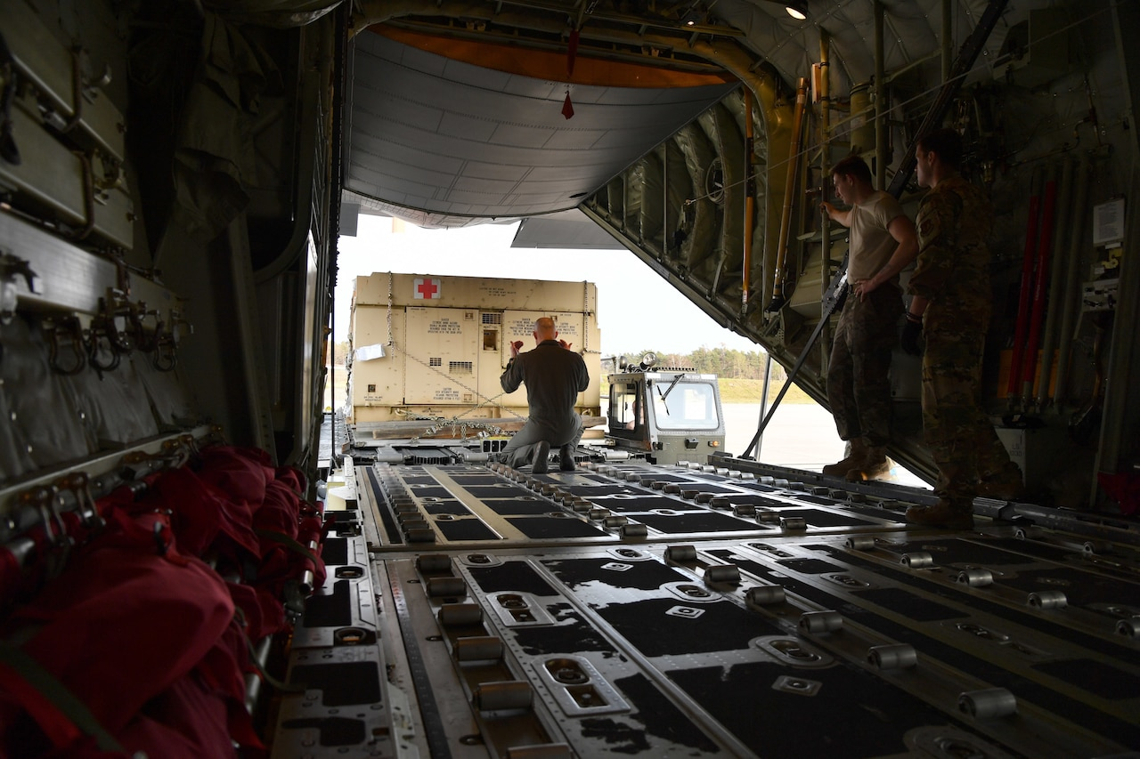 Airman guides pallet full of supplies on aircraft.