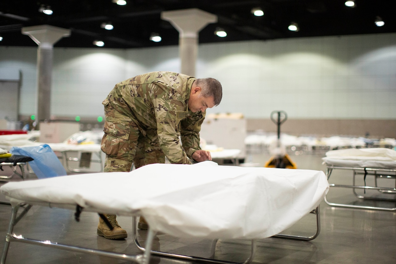A service member sets up a cot in a large room with many other cots.