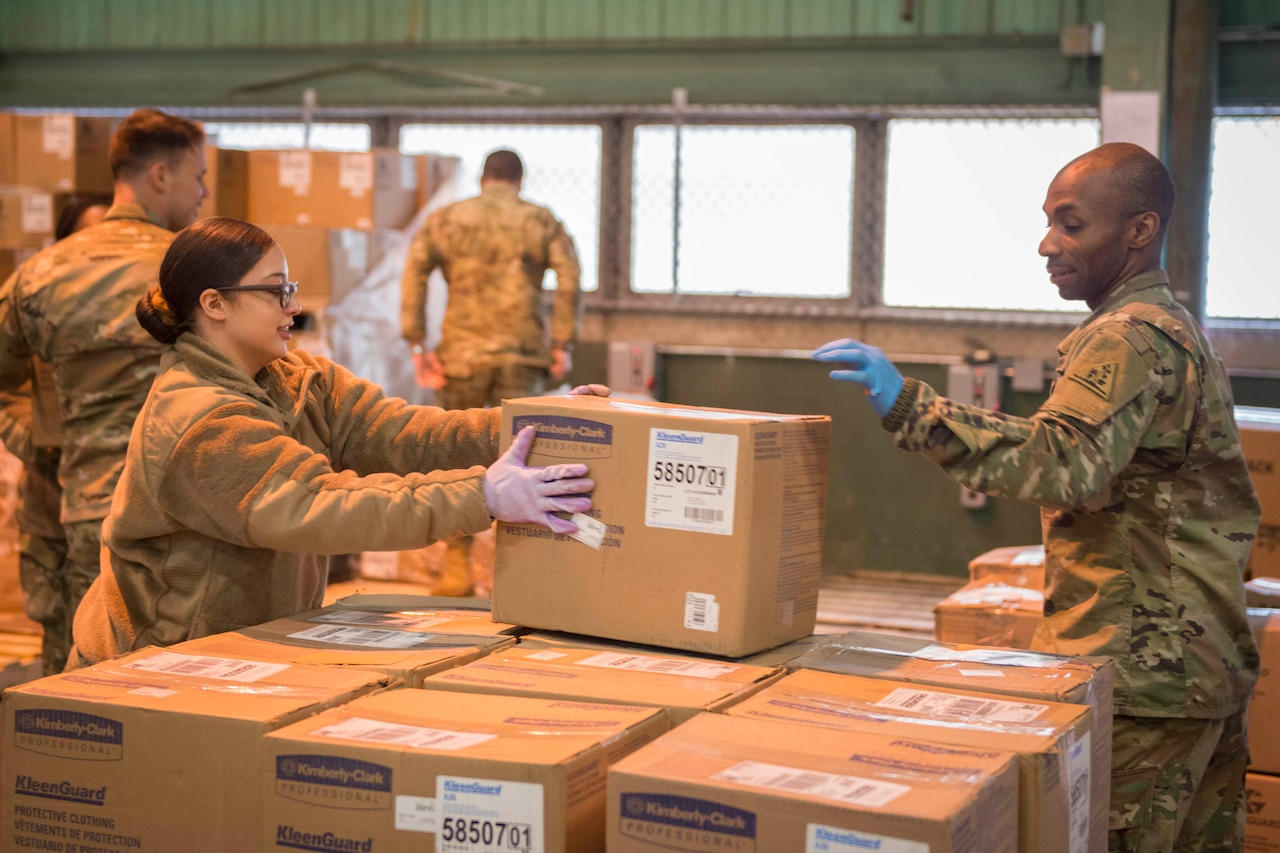 Guardsmen organize boxes in a warehouse.
