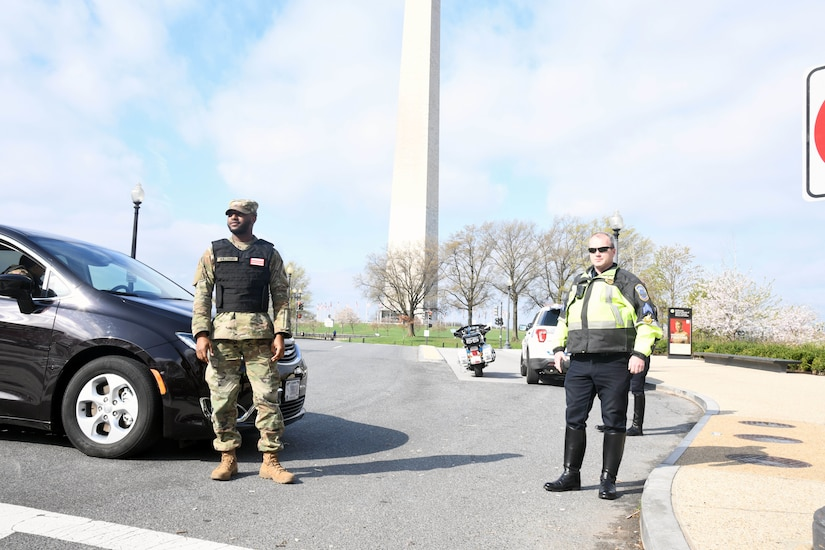 Men in uniform stand in an empty street with the Washington Monument in the background.