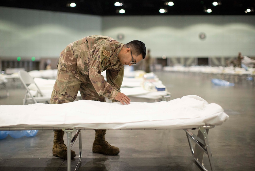 An airman puts sheets on a bed.