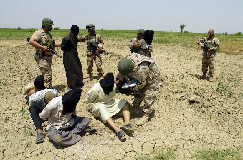 Iraqi soldiers from 3rd Brigade, 5th Iraqi army, question apprehended insurgents at detainee collection point during Operation Peninsula, in Wasit Provence, Iraq, May 20, 2005 (U.S. Army/Arthur Hamilton)