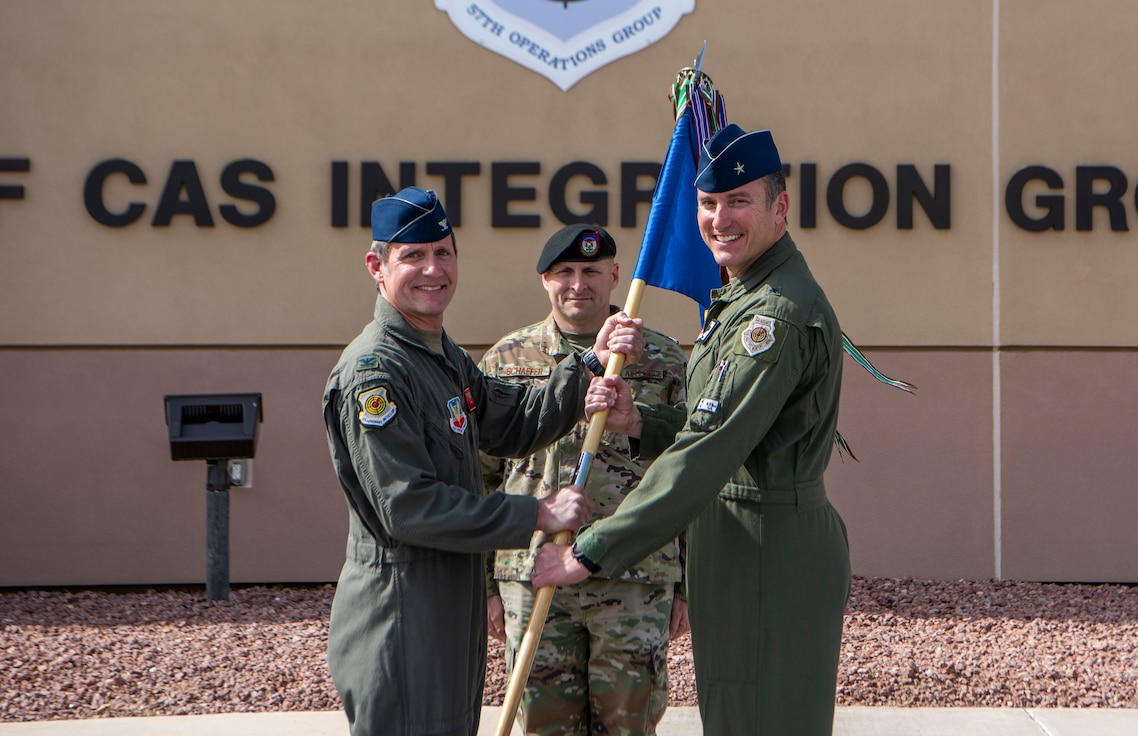 Col. John Gallemore, former 57th Adversary Tactics Group commander receives the guidon from Brig. Gen. Robert G. Novotny, 57th Wing commander as he assumes command of the 57th Operations Group (OG) as Chief Master Sgt. Thomas Schaefer II, 57th OG superintendent looks on during a change of command ceremony at Nellis Air Force Base, Nevada, March 31, 2020. The modest ceremony, adapted to support social distancing initiatives, marked the merger of the 57th Adversary Tactics Group and the 57th OG, placing both group functions under the leadership of one commander. (U.S. Air Force photo by Airman 1st Class Dwane Young)