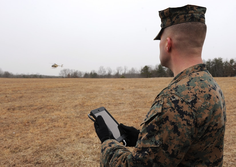 Seaman uses handheld tablet to request resupply during Office of Naval Research demonstration of Autonomous Aerial Cargo/Utility System, giving