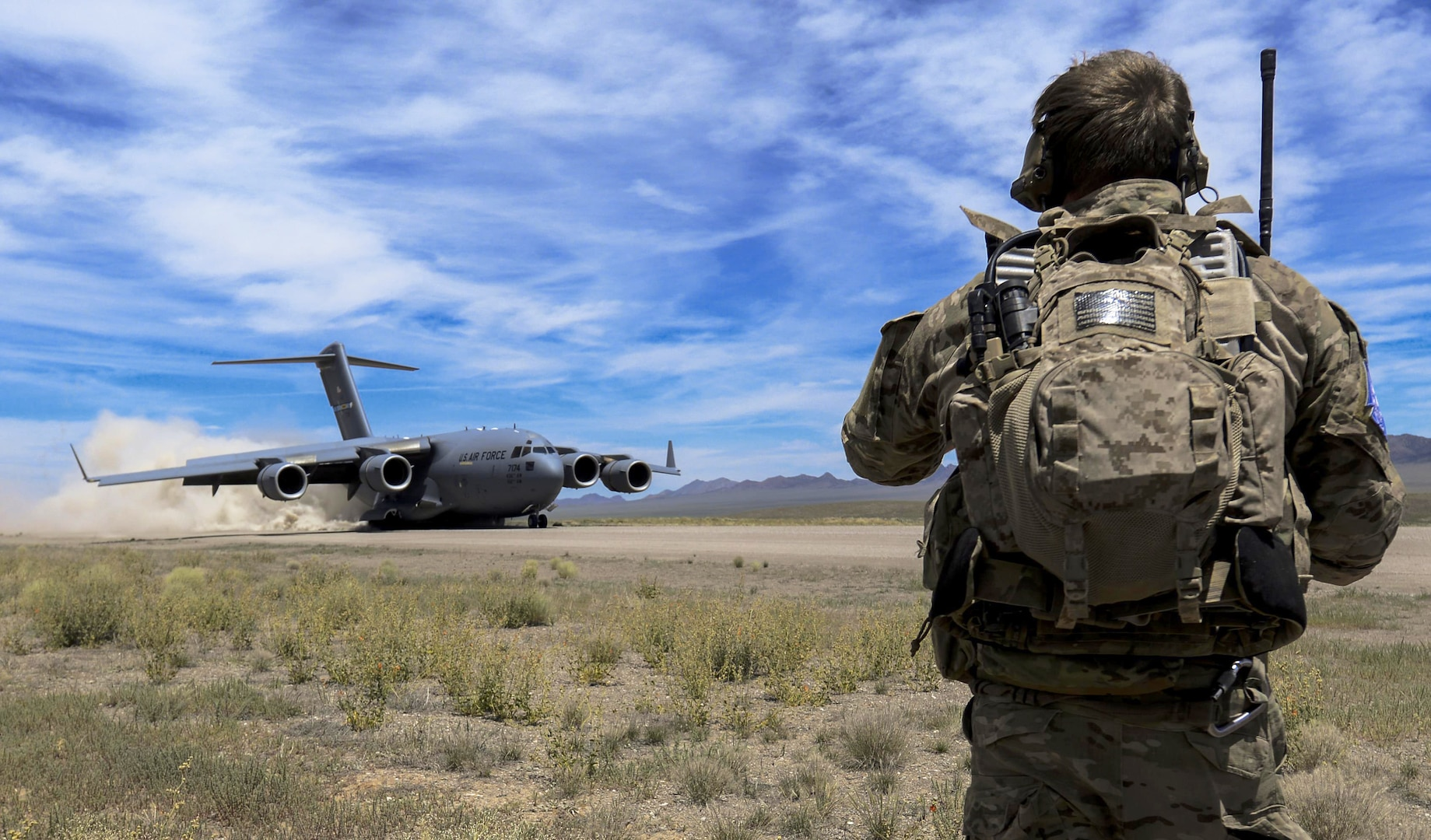 Combat controller watches as C-17 Globemaster III, assigned to 17th Weapons Squadron, Nellis Air Force Base, Nevada, lands on airstrip in Nevada Test and Training Range during joint forcible entry exercise, June 16, 2016 (U.S. Air Force/Kevin Tanenbaum)