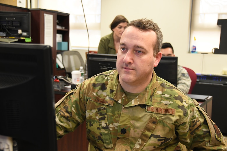 Lt. Col. Jeremy Dugan 104th Fighter Wing Emergency Operations Center commander, monitors, and coordinates with the Emergency Operation Center on critical information requests in response to COVID-19, March 30, 2020. Dugan serves in the Air National Guard in his community of Western Massachusetts. (U.S. Air National Guard Photo by Senior Master Sgt. Julie Avey)