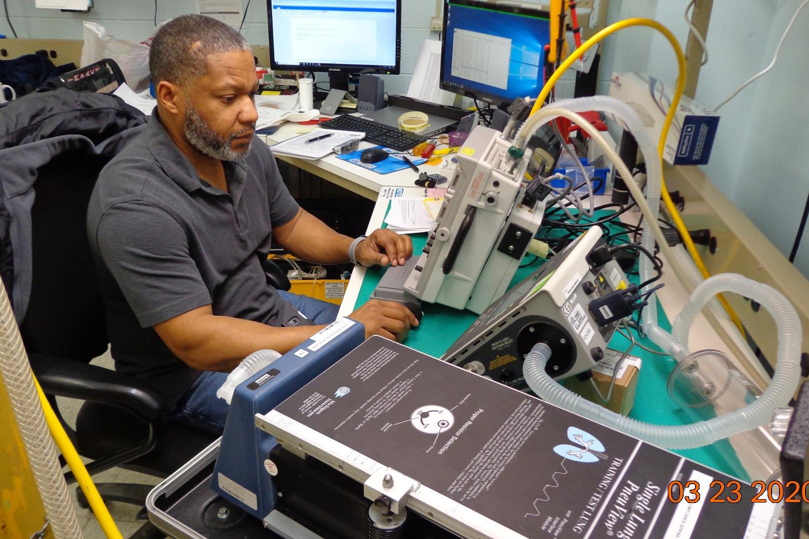 Man works on ventilator.