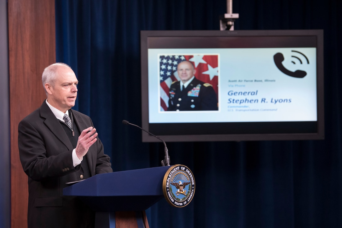 A man stands at a podium with a tv monitor next to him showing a general who is calling in to the room.