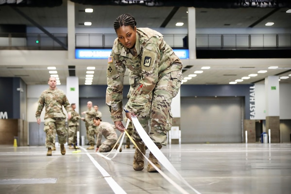 A soldier lays down tape.