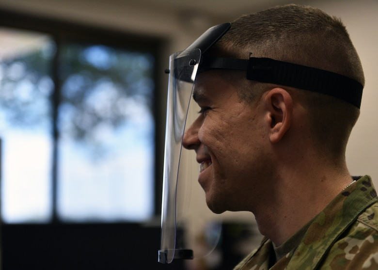 U.S. Air Force Tech. Sgt. Donald Kramer, 312th Training Squadron Special Instruments Training course instructor supervisor, demonstrates a prototype of a 3D printed face shield at the Louis F Garland Department of Defense Fire Academy on Goodfellow Air Force Base, Texas, March 31, 2020. Kramer, as well as other SPINSTRA instructors, own personal 3-D printers, providing more resources to the project. (U.S. Air Force photo by Airman 1st Class Robyn Hunsinger)
