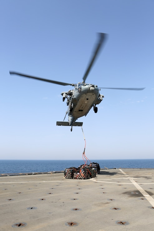 200425-M-CB805-1064 U.S. 5TH FLEET AREA OF OPERATIONS (April 25, 2020) A U.S. Navy MH-60S Sea Hawk assigned to the amphibious assault ship USS Bataan (LHD 5) delivers cargo to the amphibious dock landing ship USS Oak Hill (LSD 51) during a vertical replenishment-at-sea April 25, 2020. Oak Hill, with embarked 26th Marine Expeditionary Unit, is deployed to the U.S. 5th Fleet area of operations in support of naval operations to ensure maritime stability and security in the Central Region, connecting the Mediterranean and Pacific through the Western Indian Ocean and three strategic choke points. (U.S. Marine Corps photo by Staff Sgt. Pablo D. Morrison)