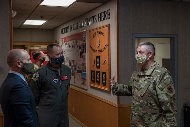 individuals with face masks on standing in flying squadron hallway
