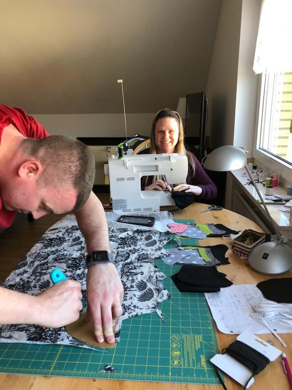 U.S. Air Force Tech. Sgt. Cameron Green, 470th Air Base Squadron paralegal, left, and his wife Katie, right, cut and sew masks for the 470th Air Base Squadron in Geilenkirchen, Germany, April 20, 2020. Sewing masks for the 470th ABS are the Green's way of giving back to the community during the COVID-19 pandemic. (U.S. Air Force photo courtesy of Master Sgt. David Zamora-Alvarez)