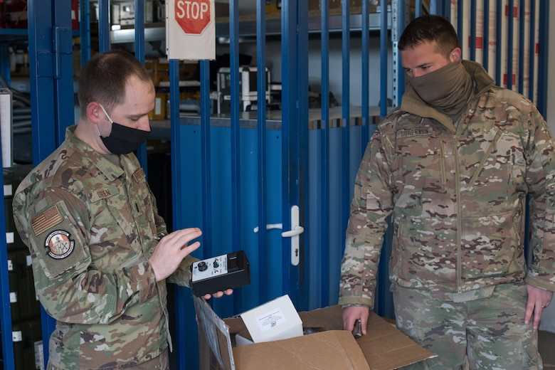 Two Airmen looking at an ion counting device.
