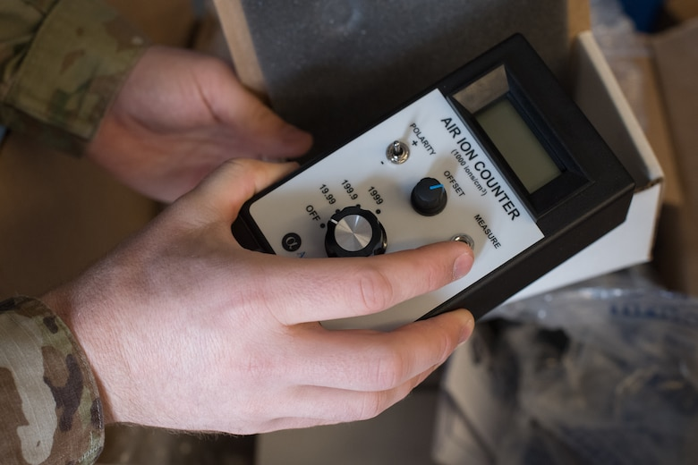 Two hands holding an ion counting device.