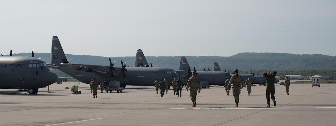 A group of Airmen walk toward a fleet of aircraft.
