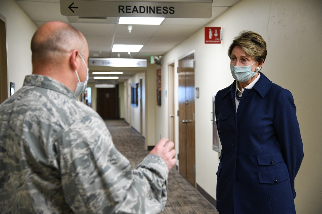 cretary of the Air Force Barbara Barrett listens to Lt. Col. Gabriel Pepper, 75th Medical Group,in a hallway at the medical clinic.