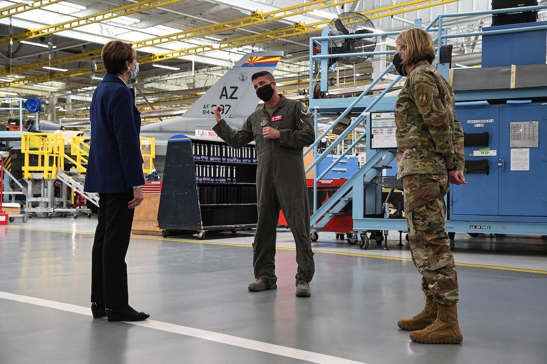 Secretary of the Air Force Barbara Barrett listens to Lt. Col. Nathan Litz, 514th Flight Test Squadron, inside a depot maintenance hangar.