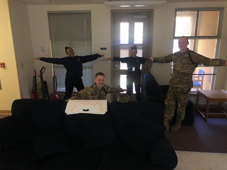 Military Training leaders with the 314th Training Squadron practice social distancing while hanging posters for Airmen morale. Due to COVID-19, the MTLs must maintain a distance of six feet apart, but they remain there to help the Airmen through boosting morale and virtual meetings. (Courtesy Photo)