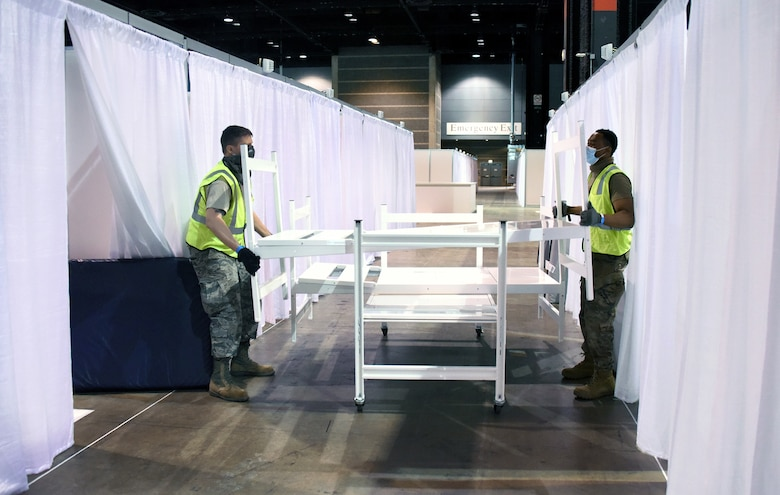 Air Force Tech. Sgt. Adam Dyer, left, and Senior Airman Koami Kunakey, both assigned to the Illinois Air National Guard's 182nd Airlift Wing, place beds in treatment cubicles at the McCormick Place Convention Center in Chicago while taking part in COVID-19 response efforts, April 11, 2020. Illinois National Guard members were assisted by a nine-person medical team from the Polish military. Since 1993, the Illinois Guard and the Polish military have been partners in the Department of Defense's State Partnership Program.