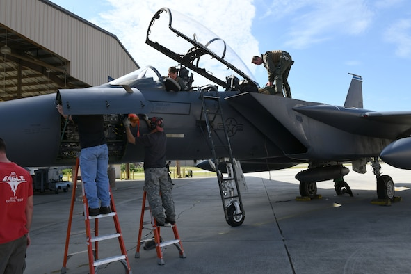 Photo shows two men getting out of an F-15 aircraft using a ladder while two other men on ladders begin working on the nose of the aircraft.
