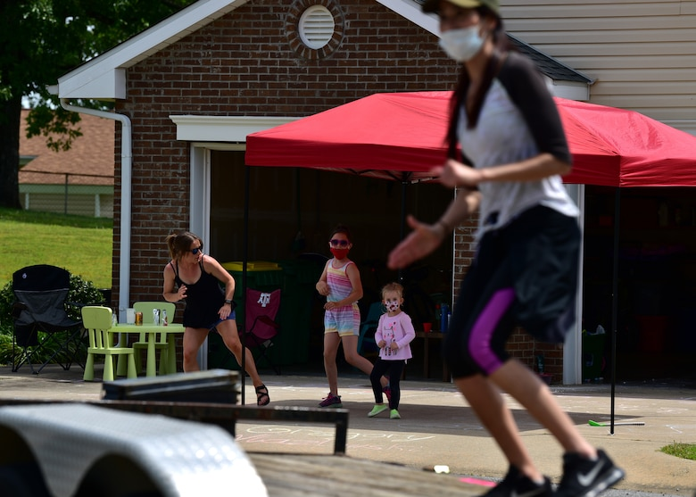 People in workout outfits stand around a trailer outside to perform exercises