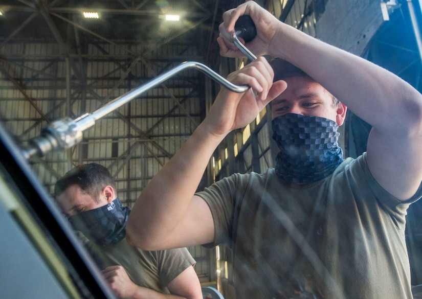 Senior Airman Dennis Powers, right, and Senior Airman Sean McGrath, left, both crew chiefs assigned to the 437th Aircraft Maintenance Squadron, removes a screw while replacing a window on the flightdeck of a C-17 Globemaster III aircraft at Joint Base Charleston, S.C., April 28, 2020. The 437th AMXS is still generating aircraft to support local training flights, missions from Air Mobility Command and supporting training for aeromedical evacuation personnel while being critically manned during the COVID-19 pandemic.The 437th AMXS is also implementing physical distancing when possible and following other Centers for Disease Control guidelines. Additionally, they have trained some of their personnel to decontaminate aircraft before and after missions to keep aircrews and 437th AMXS personnel safe. (U.S. Air Force Photo by Staff Sgt. Megan Munoz)